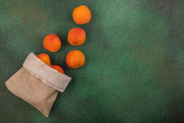 Bovenaanzicht van abrikozen morsen uit zak op groene achtergrond met kopie ruimte