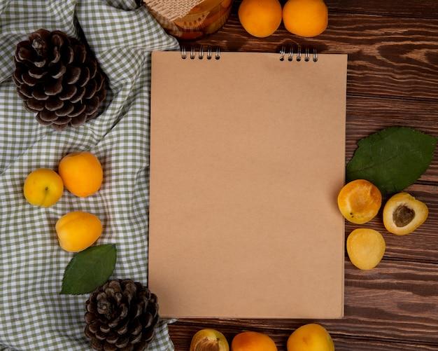 Bovenaanzicht van abrikozen rond notitieblok met dennenappels op houten achtergrond versierd met bladeren met kopie ruimte
