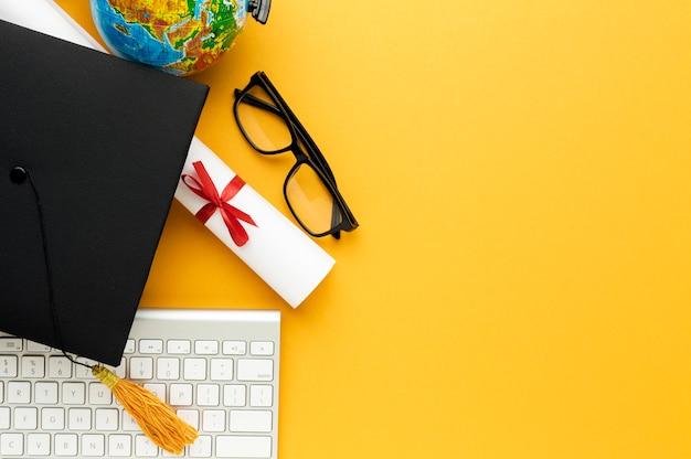 Bovenaanzicht van academische pet en bril met toetsenbord