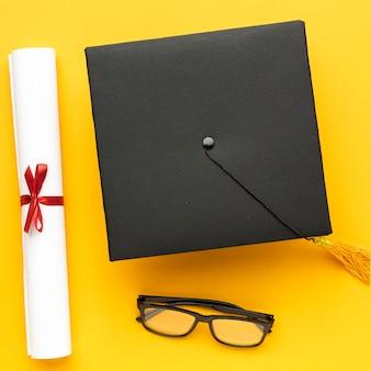 Bovenaanzicht van academische pet met diploma en bril