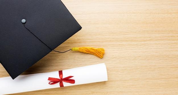 Bovenaanzicht van academische pet met diploma en kopie ruimte