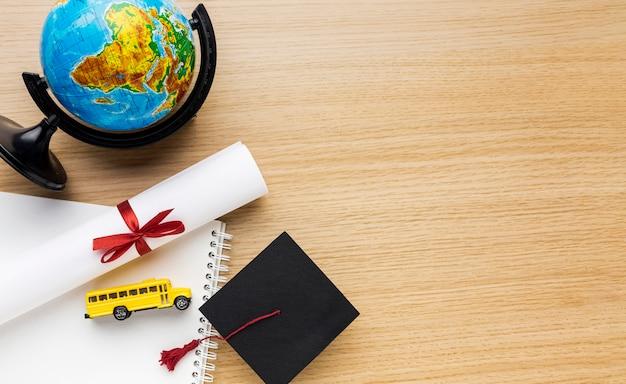 Bovenaanzicht van academische pet met globe en schoolbus