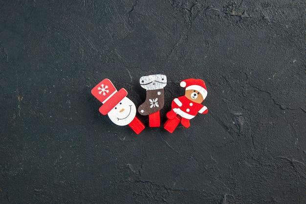 Bovenaanzicht van accessoires voor kerstversiering op een rij op een zwarte ondergrond