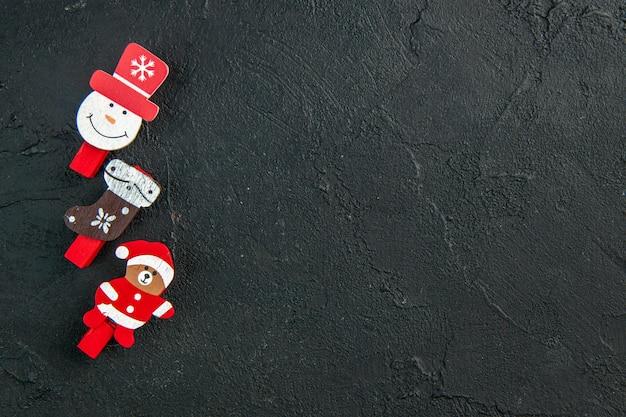 Bovenaanzicht van accessoires voor nieuwjaarsdecoratie op een rij op een zwarte ondergrond