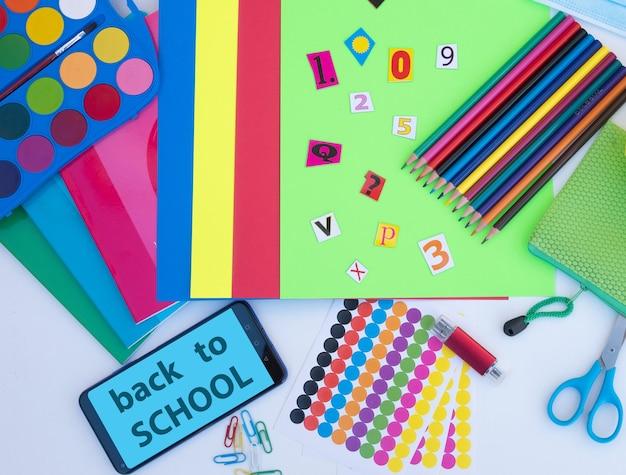 Bovenaanzicht van accessoires voor terug naar school onderwijsconceptbericht op mobiele telefoon