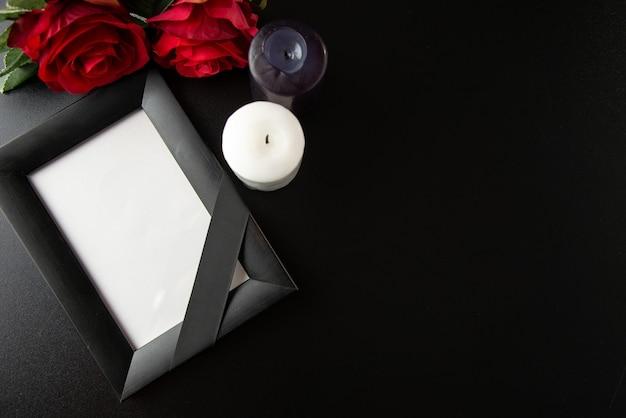 Bovenaanzicht van afbeeldingsframe met rode bloemen en kaarsen op donkere muur