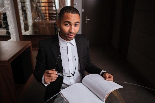 Bovenaanzicht van afrikaanse man in pak zitten met dagboek en bril in hotel
