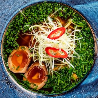 Bovenaanzicht van aisan noodlesoep met eieren gehakte groene ui en kool in een bord