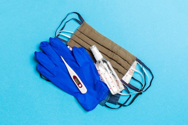 Bovenaanzicht van alcohol handdesinfecterend middel, latex handschoenen, digitale thermometer en handgemaakte herbruikbare maskers op blauw