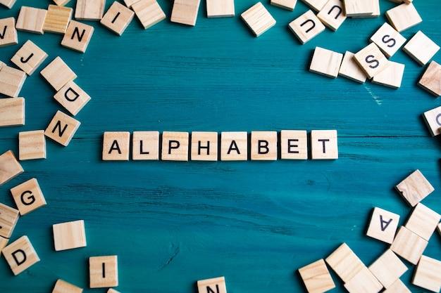Bovenaanzicht van alfabetblokken met letters op blauwe houten achtergrond. alfabet - een inscriptie en een groep letters langs de randen.