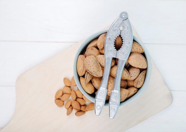 Bovenaanzicht van amandel in een kom met notenkraker op houten bord op witte achtergrond