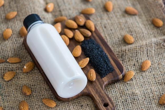 Bovenaanzicht van amandelmelk met sesam in een plastic fles met amandelen, noot en sesamzaad op rustieke stoffen houten dienblad en tafel. concept van alternatieve biologische gezonde detox en dieet eten en drinken.