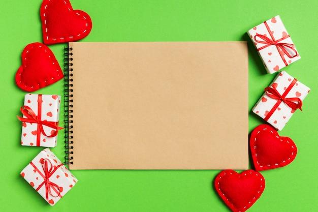 Bovenaanzicht van ambachtelijke notebook omringd met geschenkdozen en harten