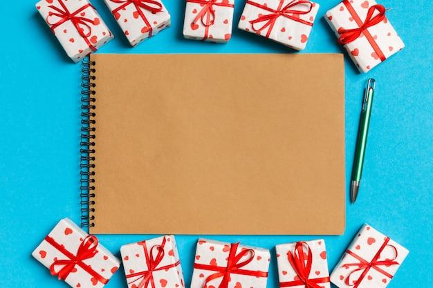 Bovenaanzicht van ambachtelijke notebook omringd met geschenkdozen
