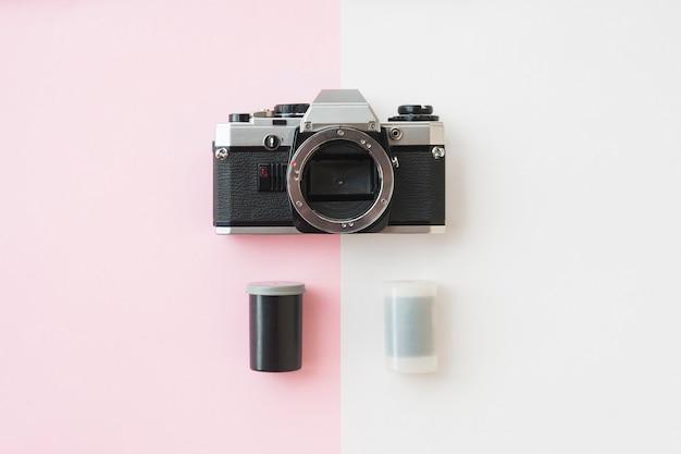 Bovenaanzicht van analaog-spiegelreflexcamera met 35 mm-filmbussen op roze
