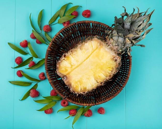 Bovenaanzicht van ananas half in mand met patroon van frambozen en bladeren op blauwe ondergrond