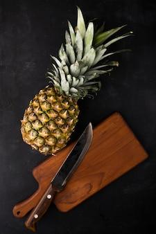 Bovenaanzicht van ananas met mes op snijplank op zwarte ondergrond