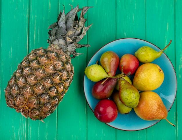 Bovenaanzicht van ananas met perziken in plaat op groene ondergrond