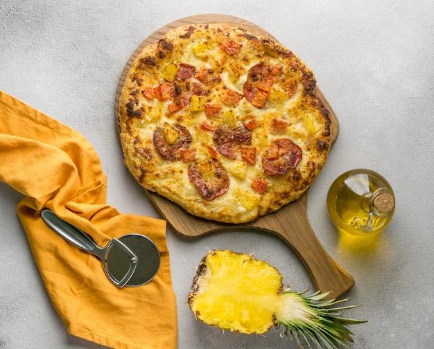 Bovenaanzicht van ananas pizza met olie en cutter