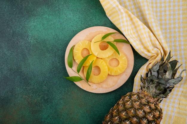 Bovenaanzicht van ananas segmenten en ananas op geruite doek en groen oppervlak