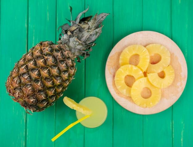 Bovenaanzicht van ananassap met ananasschijven op snijplank en ananas op groene ondergrond