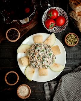 Bovenaanzicht van appel salade plaat met veldsla, kip, mayonaise en rozijnen