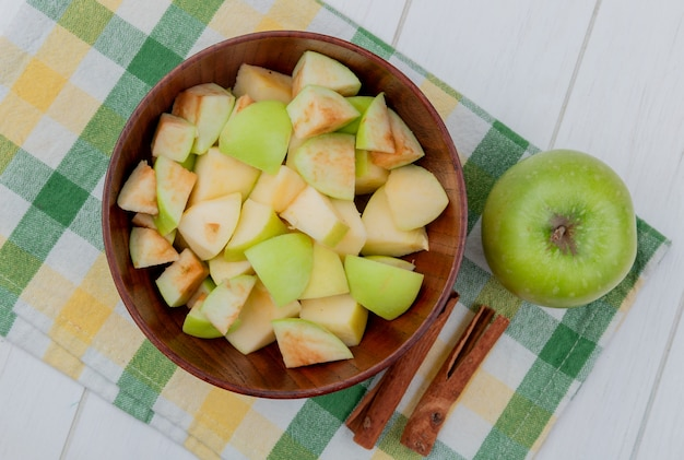 Bovenaanzicht van appelblokjes in kom en geheel met kaneel op geruite doek en houten