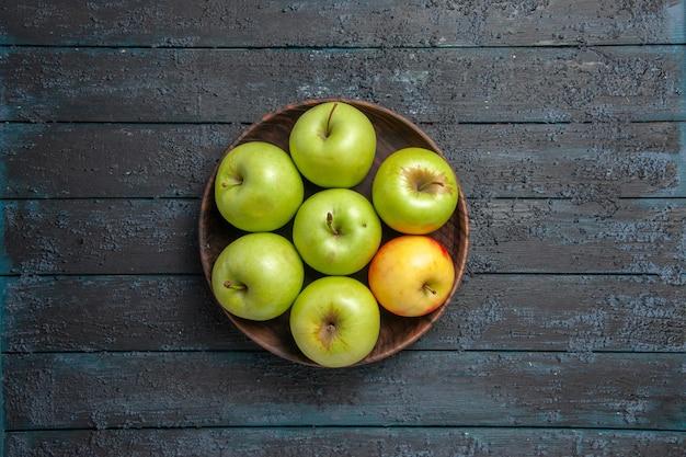 Bovenaanzicht van appels in de verte op tafelschaal van zeven groen-geel-rode appels op grijze tafel