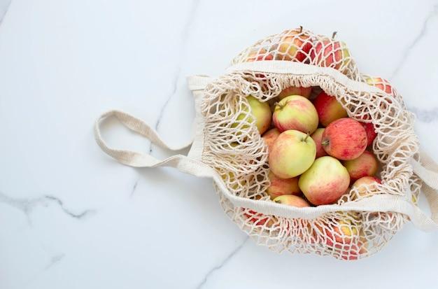 Bovenaanzicht van appels in een milieuvriendelijke stringtas op een witte achtergrond.