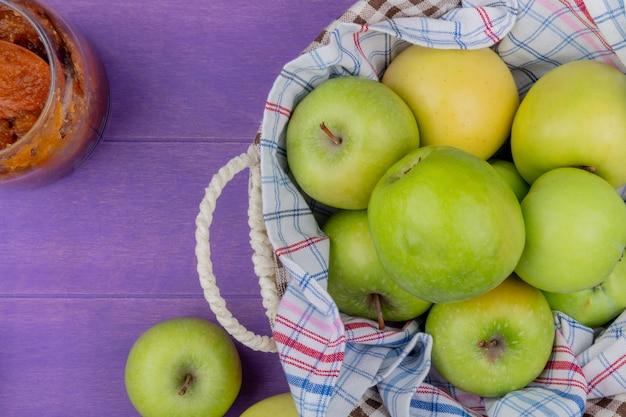 Bovenaanzicht van appels in mand met appeljam op paarse achtergrond