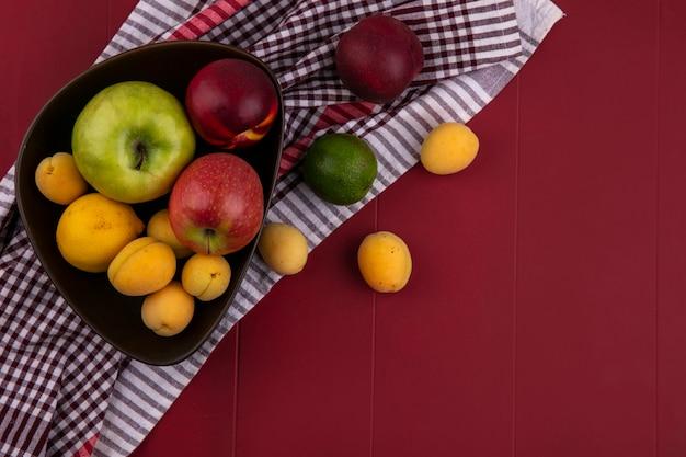 Bovenaanzicht van appels met perziken en abrikoos in een kom op een rode ondergrond