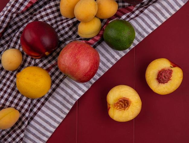 Bovenaanzicht van appels met perziken en abrikoos op een rode ondergrond