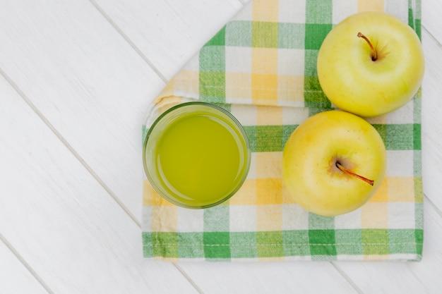 Bovenaanzicht van appelsap en groene appels op plaid doek en houten achtergrond met kopie ruimte