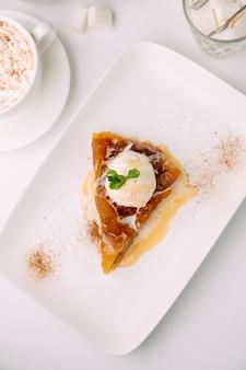 Bovenaanzicht van appeltaart met gesmolten vanille-ijs op de witte plaat in het café
