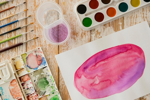 Bovenaanzicht van aquarel met palet en borstels