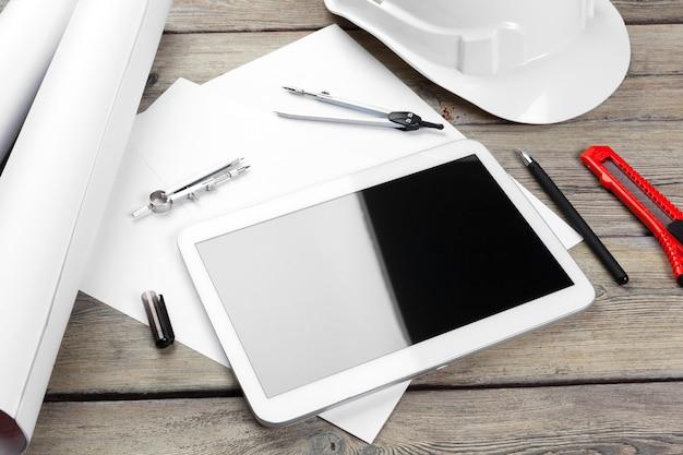 Bovenaanzicht van architect werkplek met blauwdruk papier en digitale tablet met leeg scherm