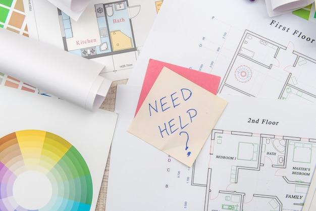 Bovenaanzicht van architecturale blauwdrukken met materiaalmonster op creatief bureau.