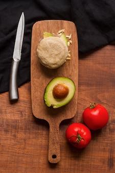 Bovenaanzicht van arepa met avocado en tomaten