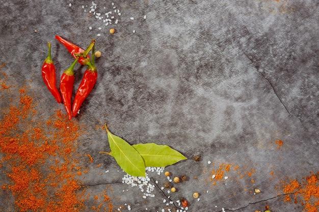Bovenaanzicht van aromatische droge kruiden en specerijen op grijze achtergrond.