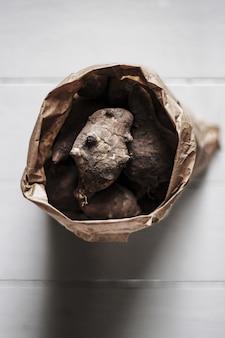 Bovenaanzicht van artisjokken van jeruzalem in een bruine zak