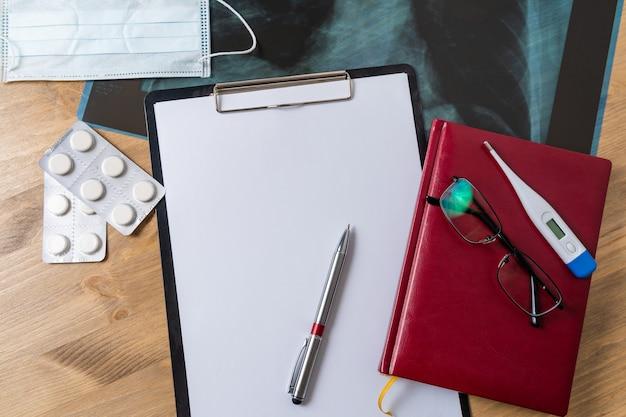 Bovenaanzicht van arts bureau tafel, blanco papier op klembord met pen. kopieer ruimte.