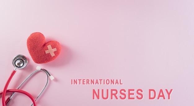 Bovenaanzicht van arts stethoscoop en rood hart op roze achtergrond met internationale verpleegkundigen dag tekst