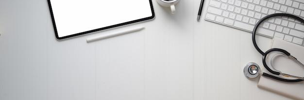 Bovenaanzicht van arts werkruimte met digitale apparaten, stethoscoop en kopie ruimte