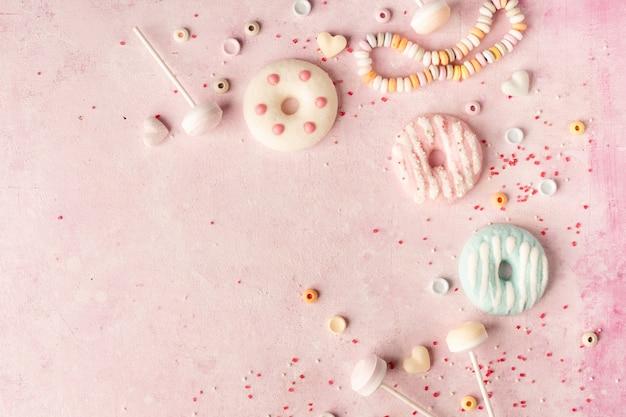 Bovenaanzicht van assortiment geglazuurde donuts en snoep met kopie ruimte
