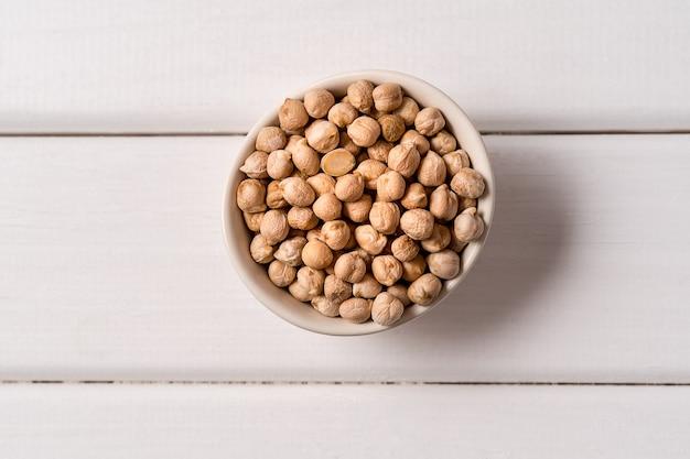 Bovenaanzicht van assortiment van erwten, linzen, bonen en peulvruchten over witte houten.