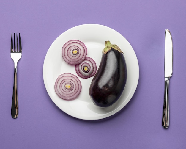 Bovenaanzicht van aubergine en ui op plaat met bestek