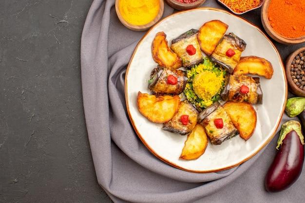 Bovenaanzicht van aubergine rolt gekookt gerecht met gebakken aardappelen en kruiden op zwart