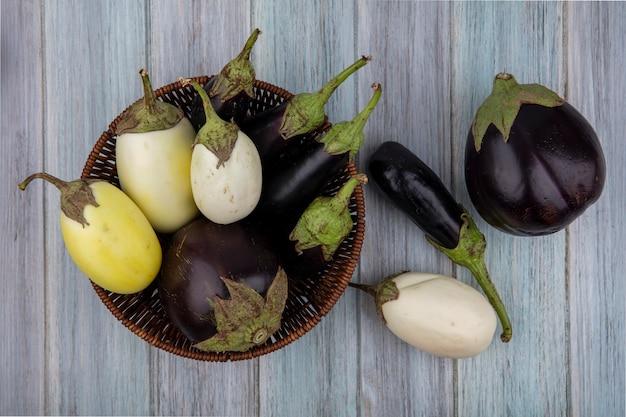 Bovenaanzicht van aubergines in mand en op houten achtergrond