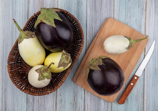 Bovenaanzicht van aubergines in mand en op snijplank met mes op houten achtergrond