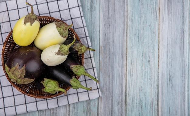 Bovenaanzicht van aubergines in mand op geruite doek op houten achtergrond met kopie ruimte